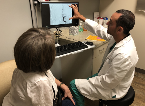 Andrew Hines, MD, reviews the imaging from a stroke embolectomy case he performed 3 months prior with a patient in the IR stroke clinic at Carolinas Healthcare-NorthEast. Six body IRs provide 100 percent of the endovascular stroke coverage at this hospital site.