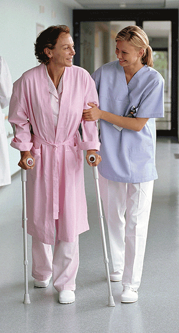 Medical professional helping female patient walk