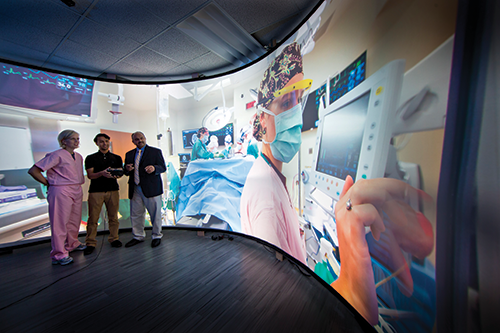 Three individuals looking at giant screen with video of procedure