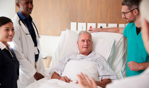 Team of physicians stands around patient in bed