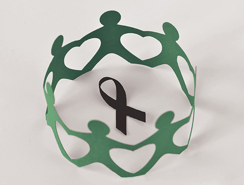 Paper cut-out people hold hands around a black ribbon for melanoma awareness