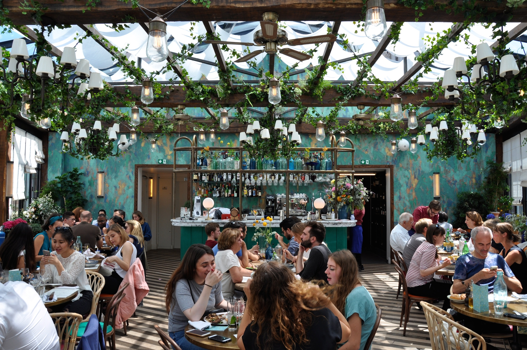 The Big Mamma Group offers Trendy, Fresh, Authentic Italian Dining in Paris at several locations including Pink Mamma in South Pigalle, where there are tables under a glass roof adorned with plants.