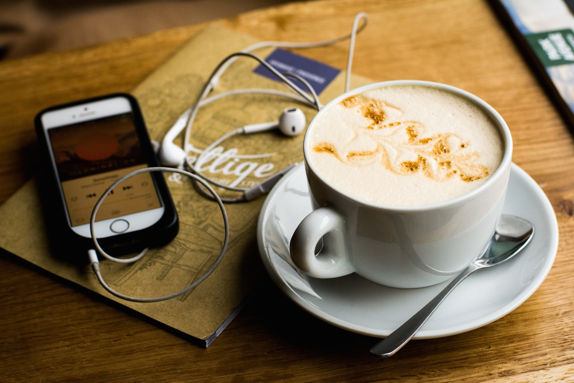 HiP Paris Blog rounds up the top French podcasts to enjoy while you have your coffee, like this creamy Cappuccino on a wooden table, next to a phone with a podcast on the screen.