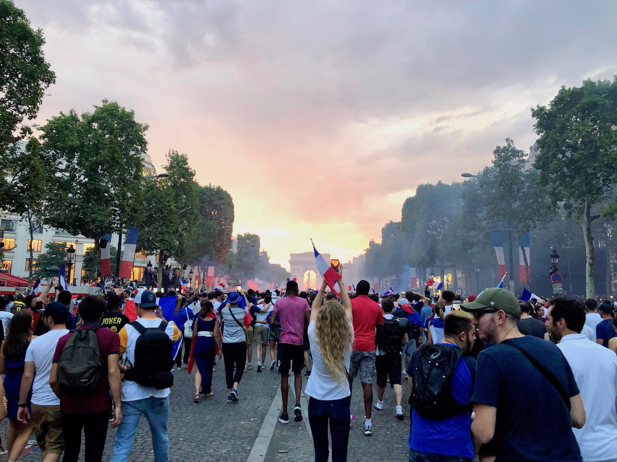 World Champions 2018: France Wins The World Cup Again and the French celebrate on the Champs Elysées waving flags at sunset with the Arc de Triomphe in the background.