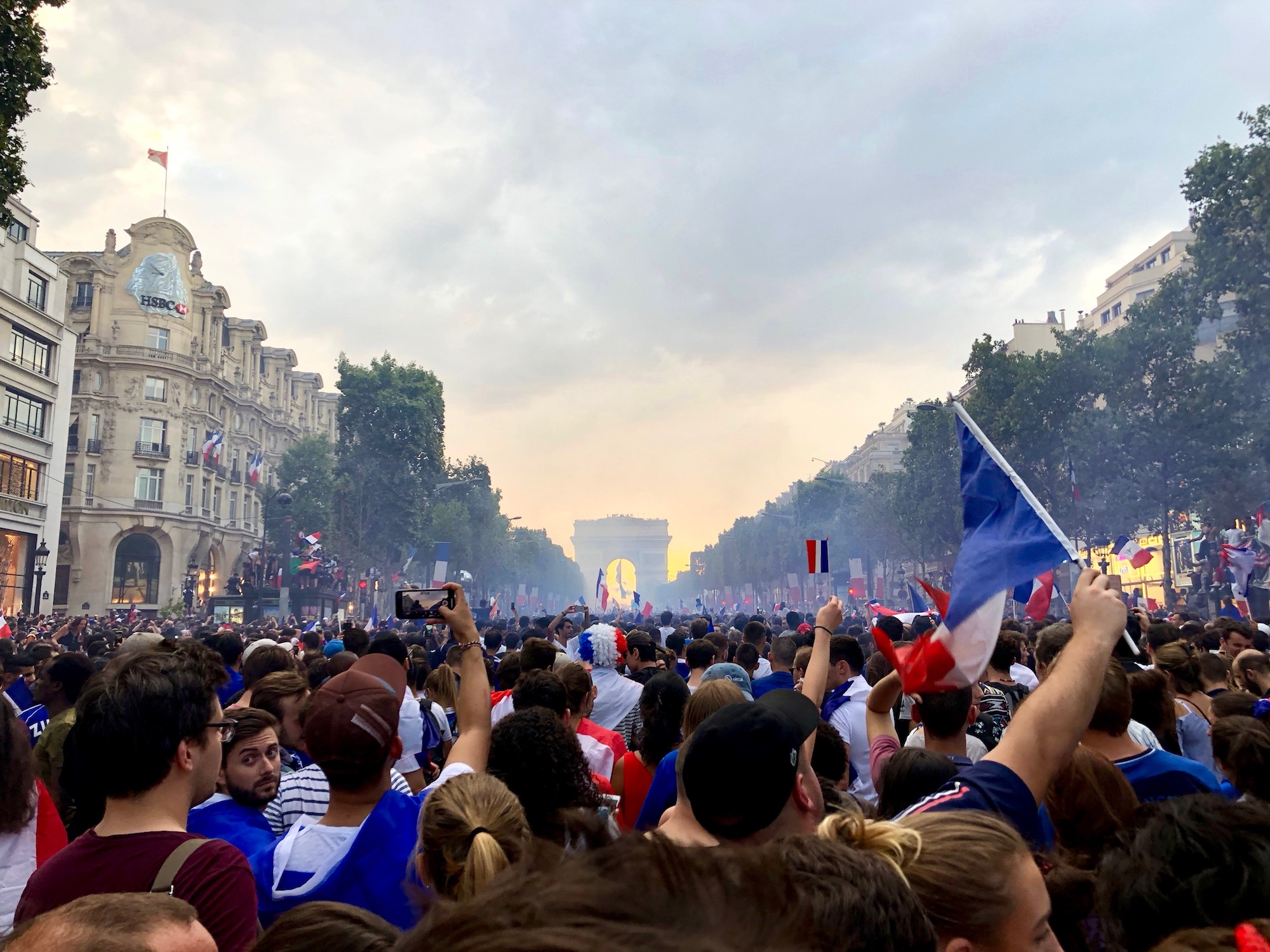 When France won the world cup in 2018, crowds celebrated on the Champs Elysées, waving French flags with the Arc de Triomphe in the background.