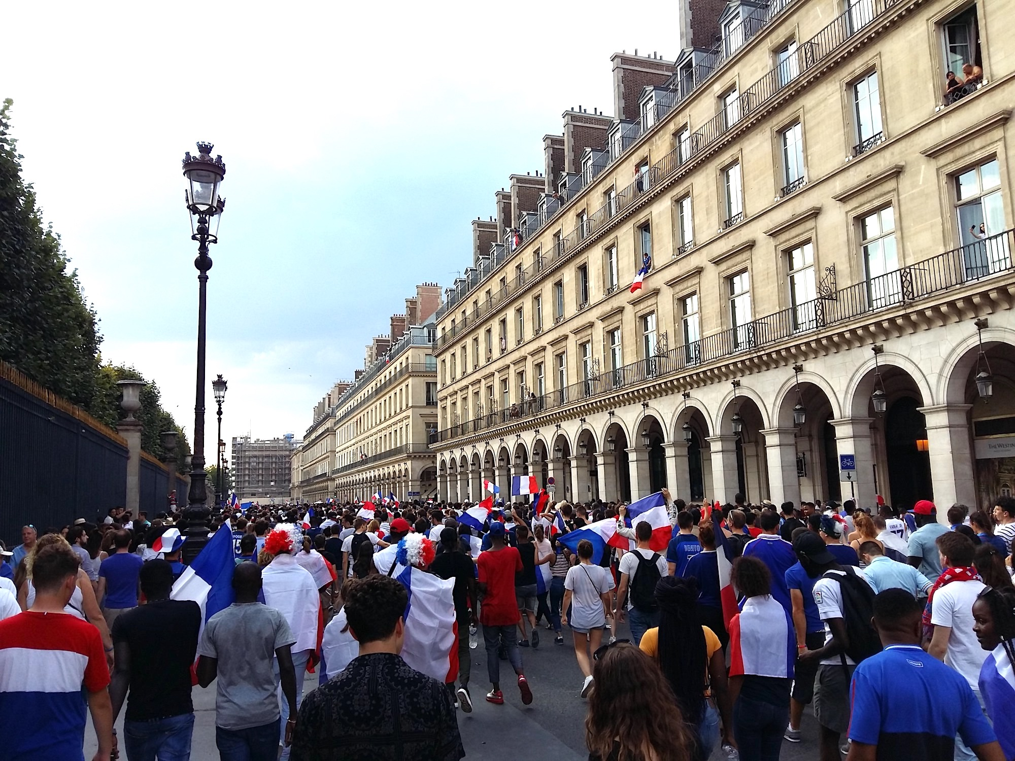 Crowds of people celebrating wrapped in French flags on the Rue de Rivoli when France won the football world cup 2018.