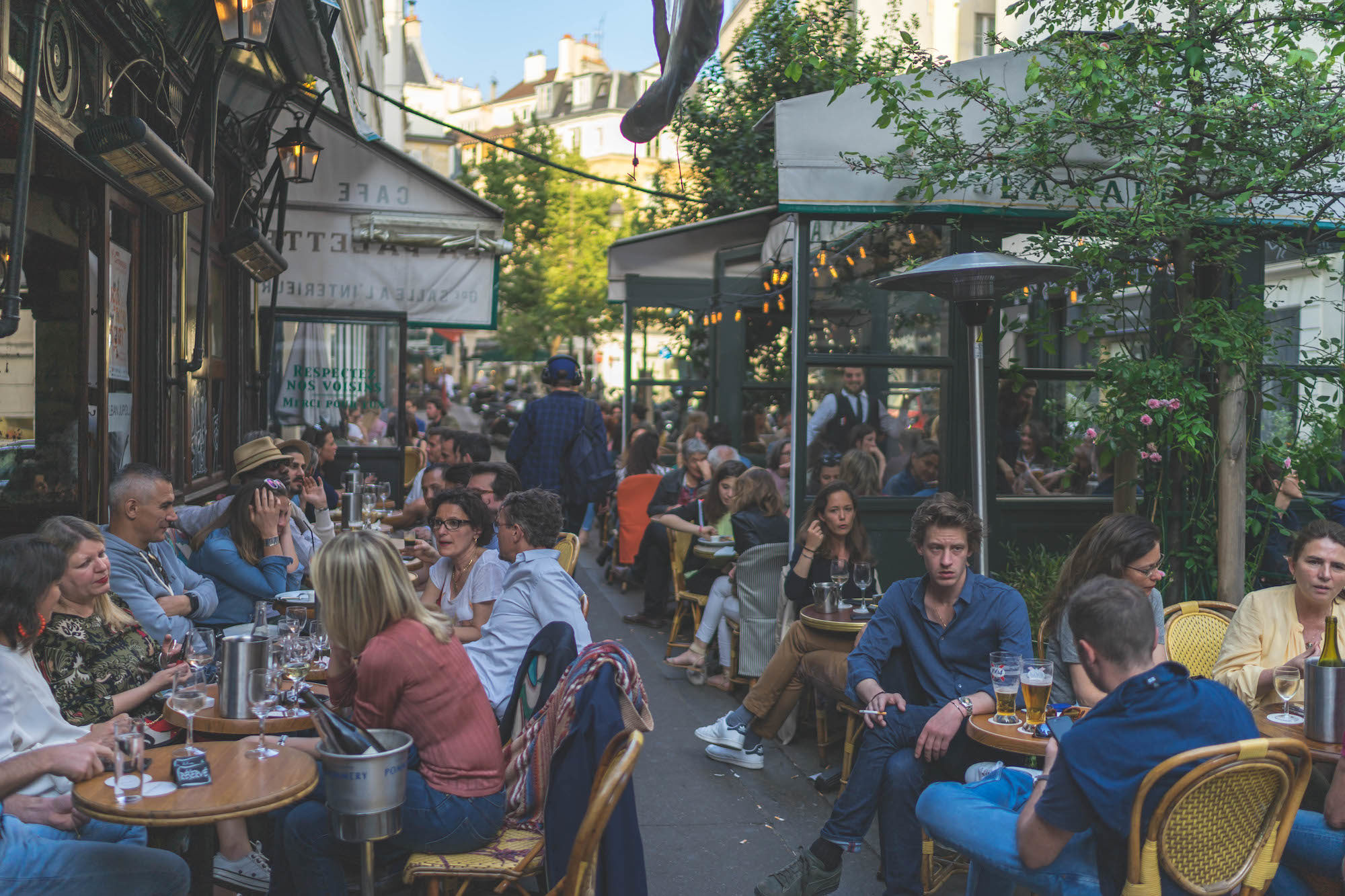 Paris in the summer teems with locals hanging out on cafe terraces, enjoying the weather.
