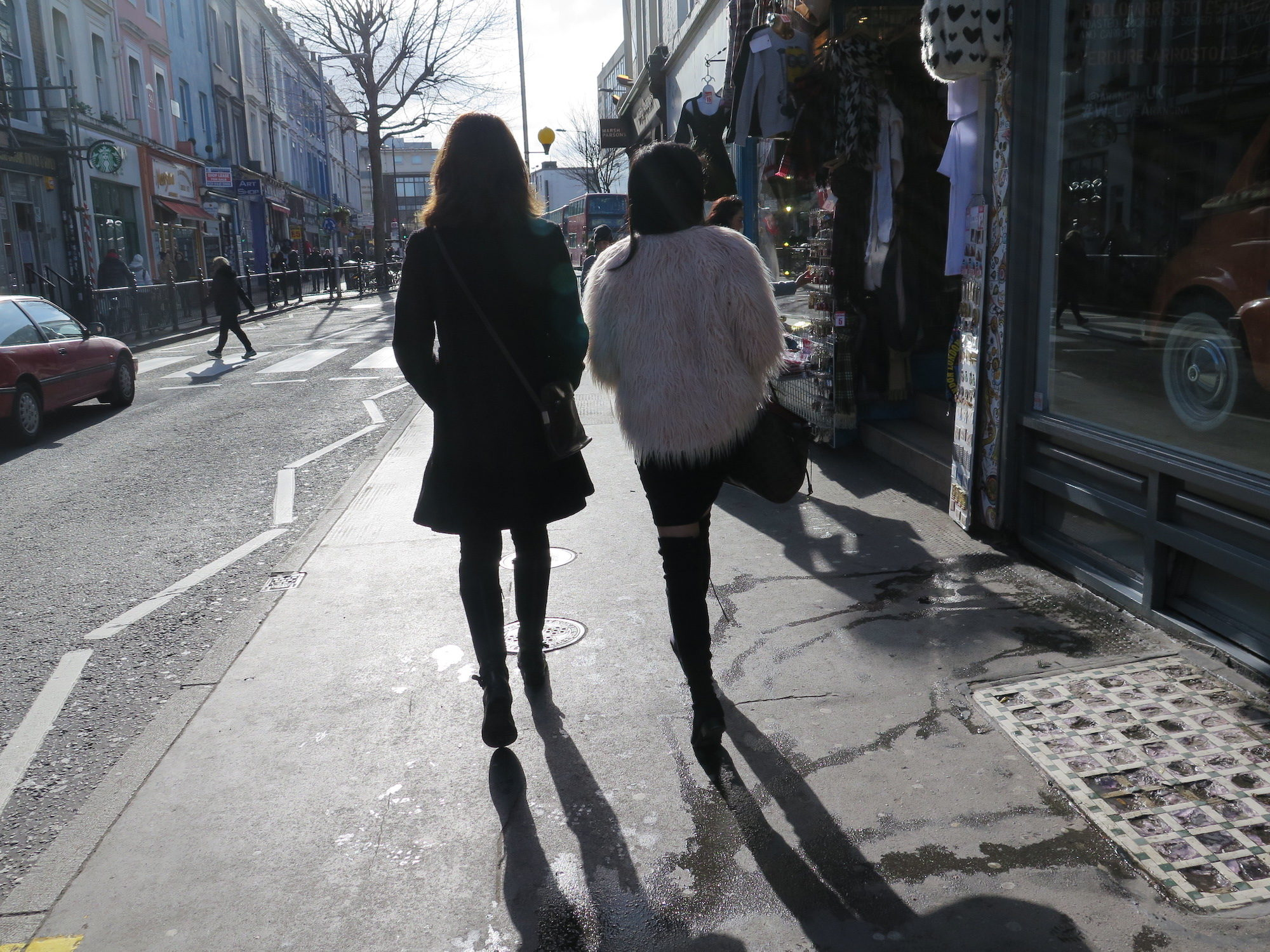 Two girls walking along a street in the London sunshine, one of them wears a fluffy pink jacket.