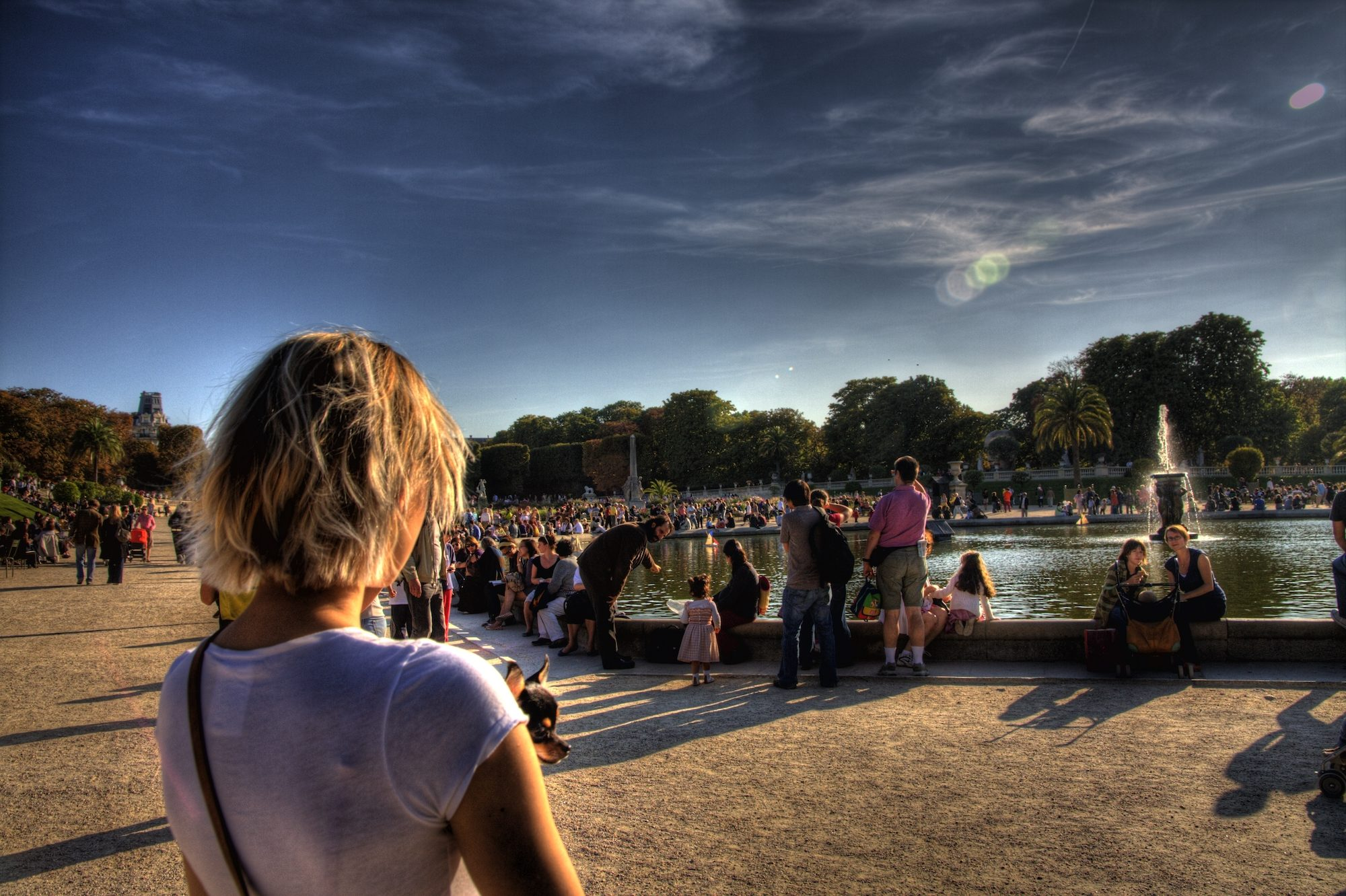A woman looks at the crowds sitting around the pond at the Tuileries Gardens, one of HiP Paris Blog's best places to tan in Paris in summer.