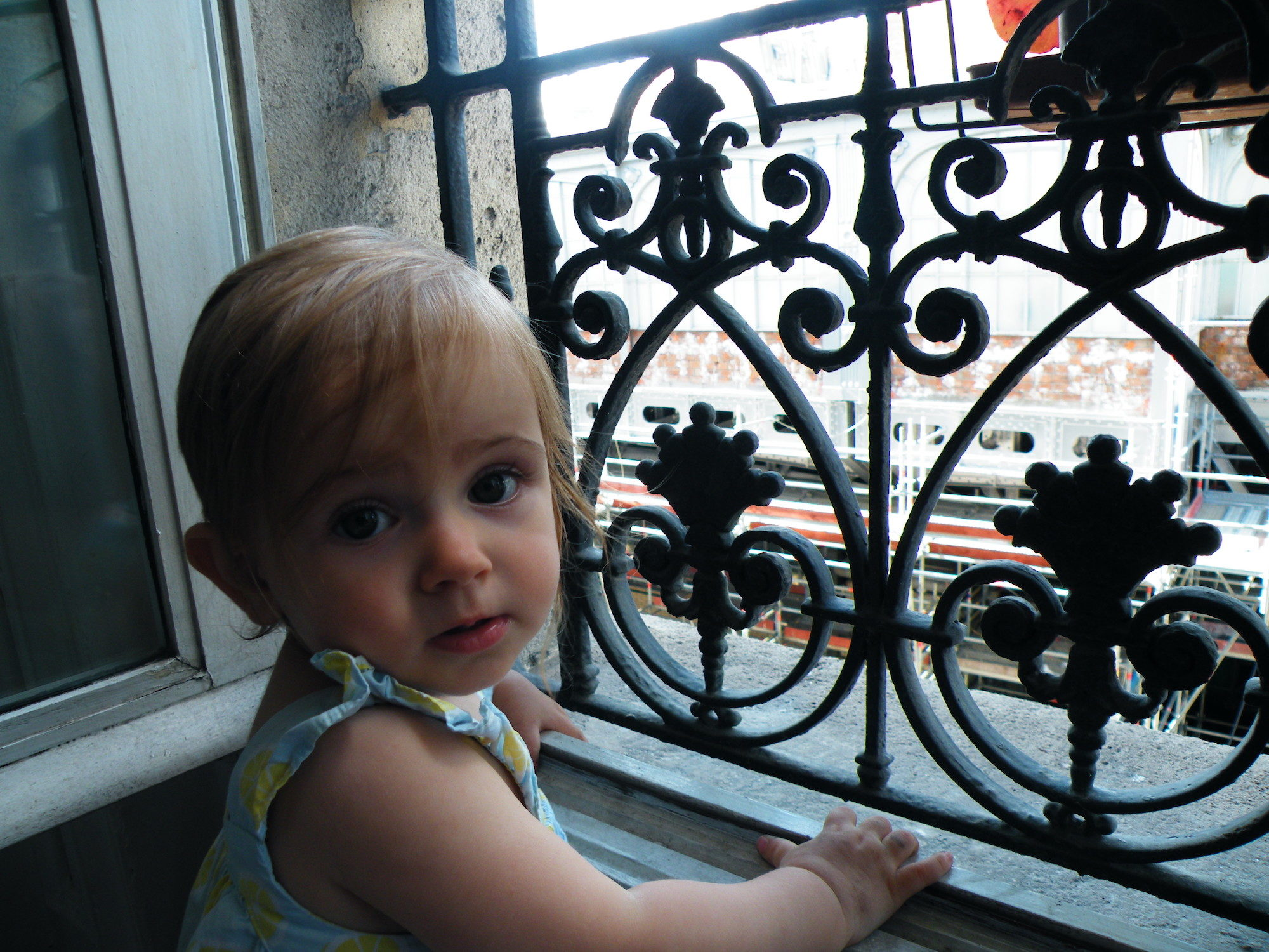 HiP Paris Blog explores what it's like traveling to Paris with babies like this cute little girl looking out of a Paris apartment window.