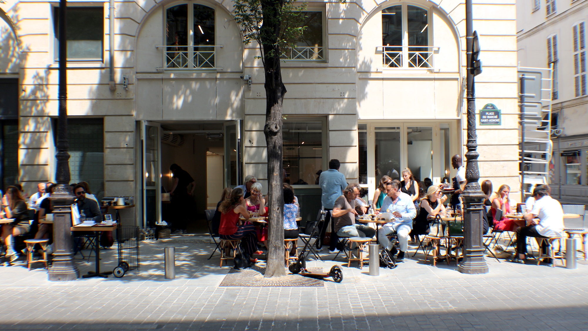Maison Plisson coffee shop near the Louvre is set on a sunny street corner with an outdoor terrace for enjoying the summer sun.