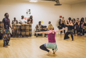 A student at an African dance class at the Momboye studio in Paris performs in front of the teacher, musicians and other students.