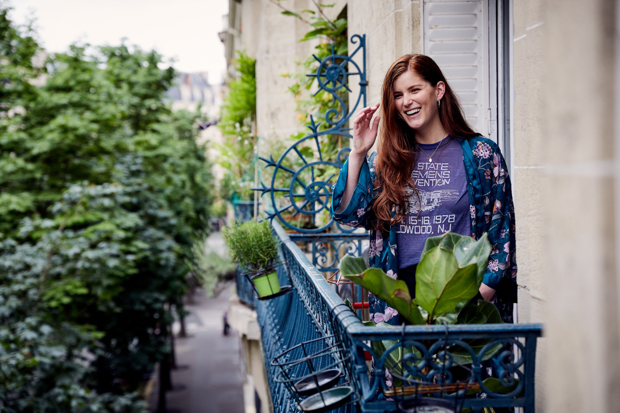 A woman living in Paris and laughing, while standing on her balcony looking out onto a leafy square.