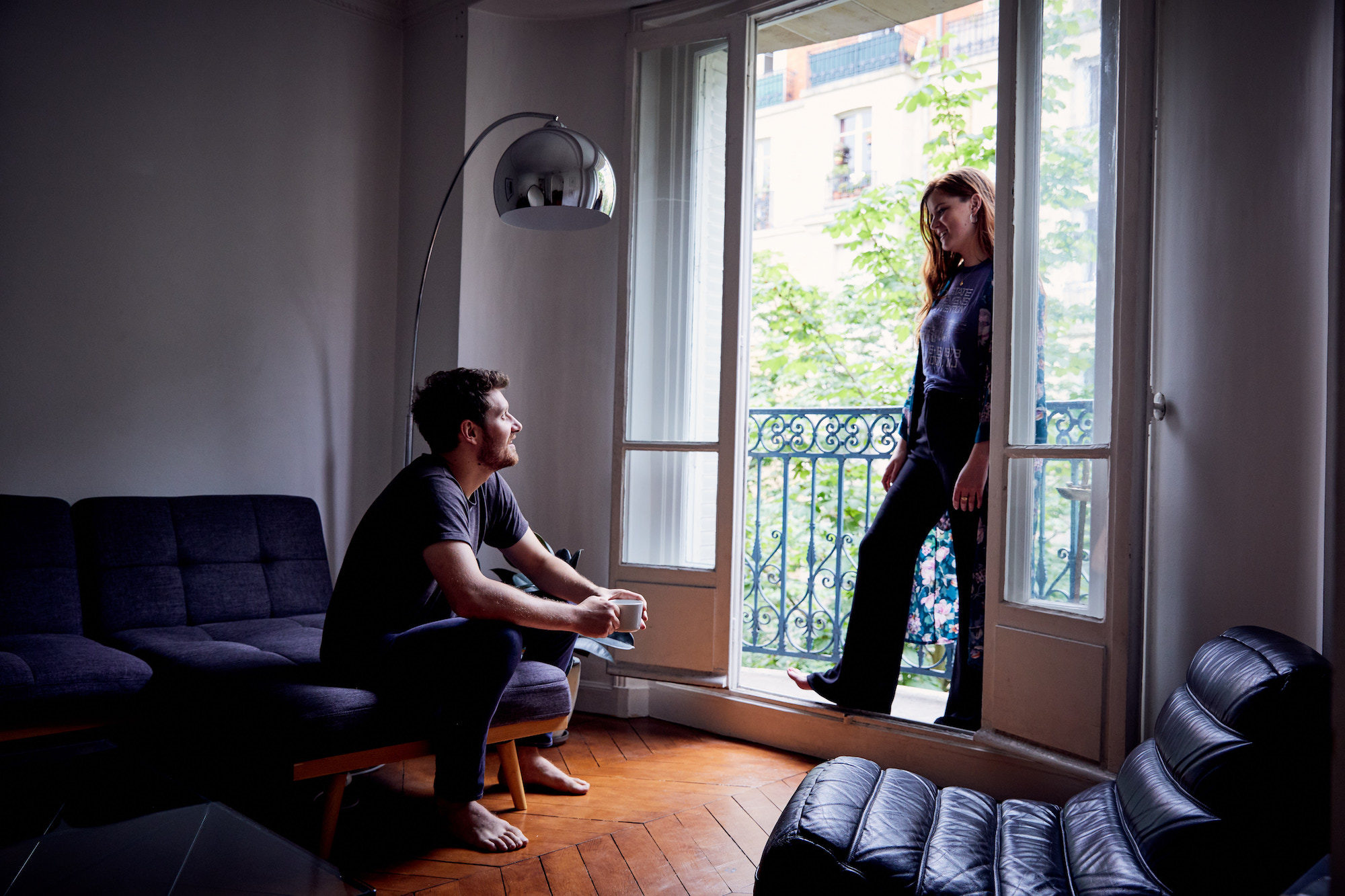 A young man and woman living in Paris and talking in their apartment which has wooden floors and a window that opens onto a balcony.