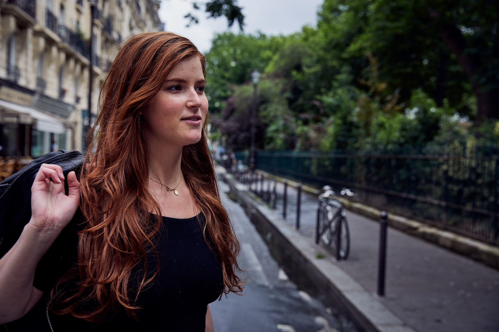 A young red-haired woman with a jacked slung over her right shoulder who loves living in Paris.