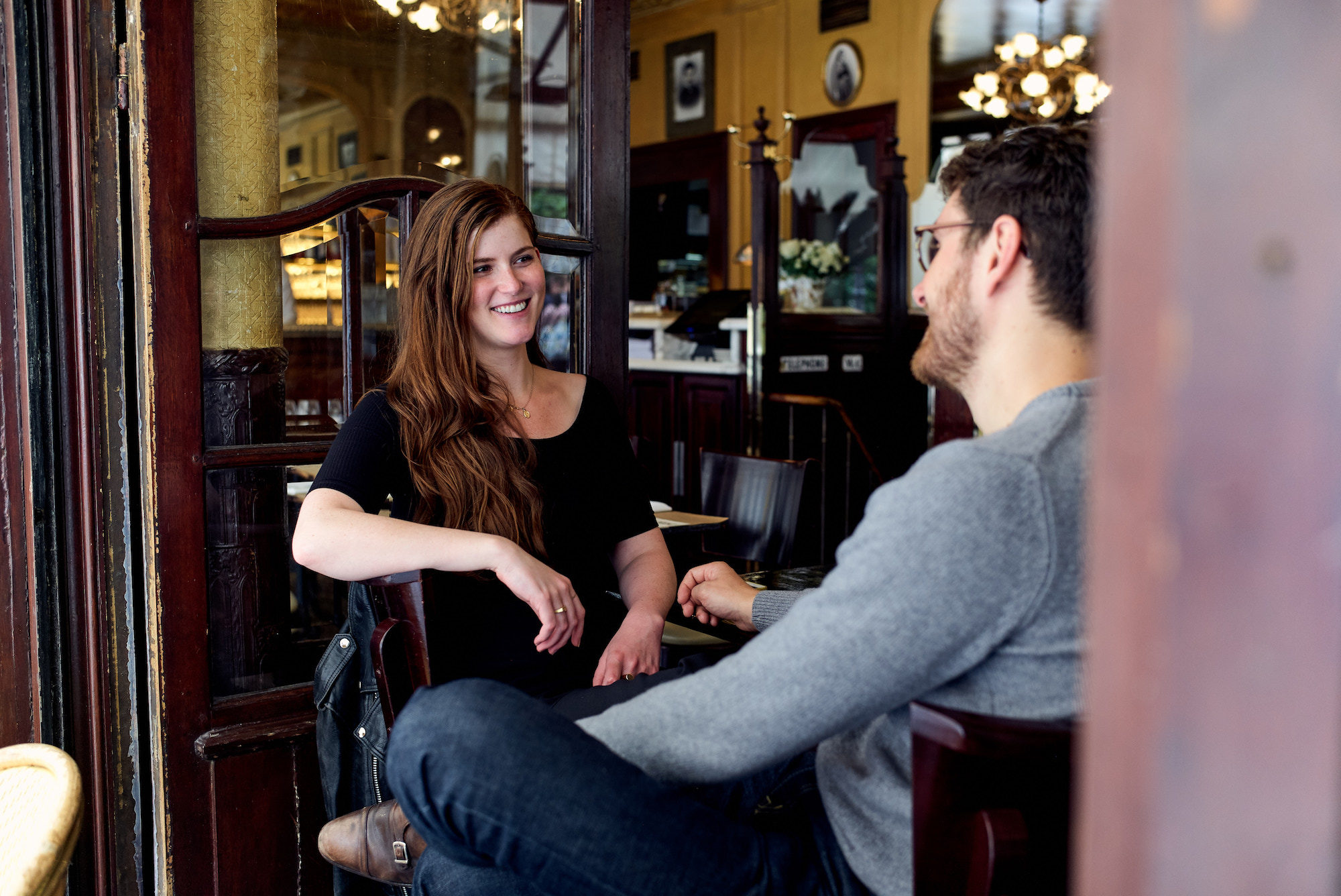 A young man and woman living in Paris and sat in a typical Paris bistro with wood interiors.