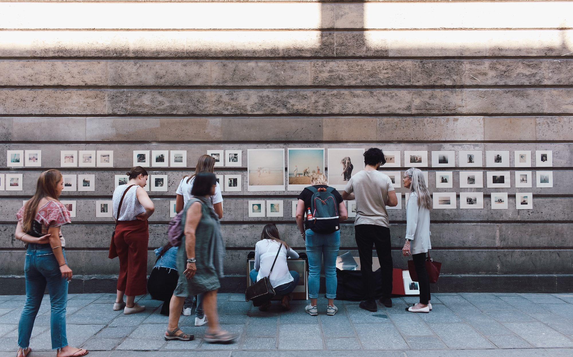 People stopping to look at a makeshift photography exhibition on the streets of the Marais neighbourhood in Paris.