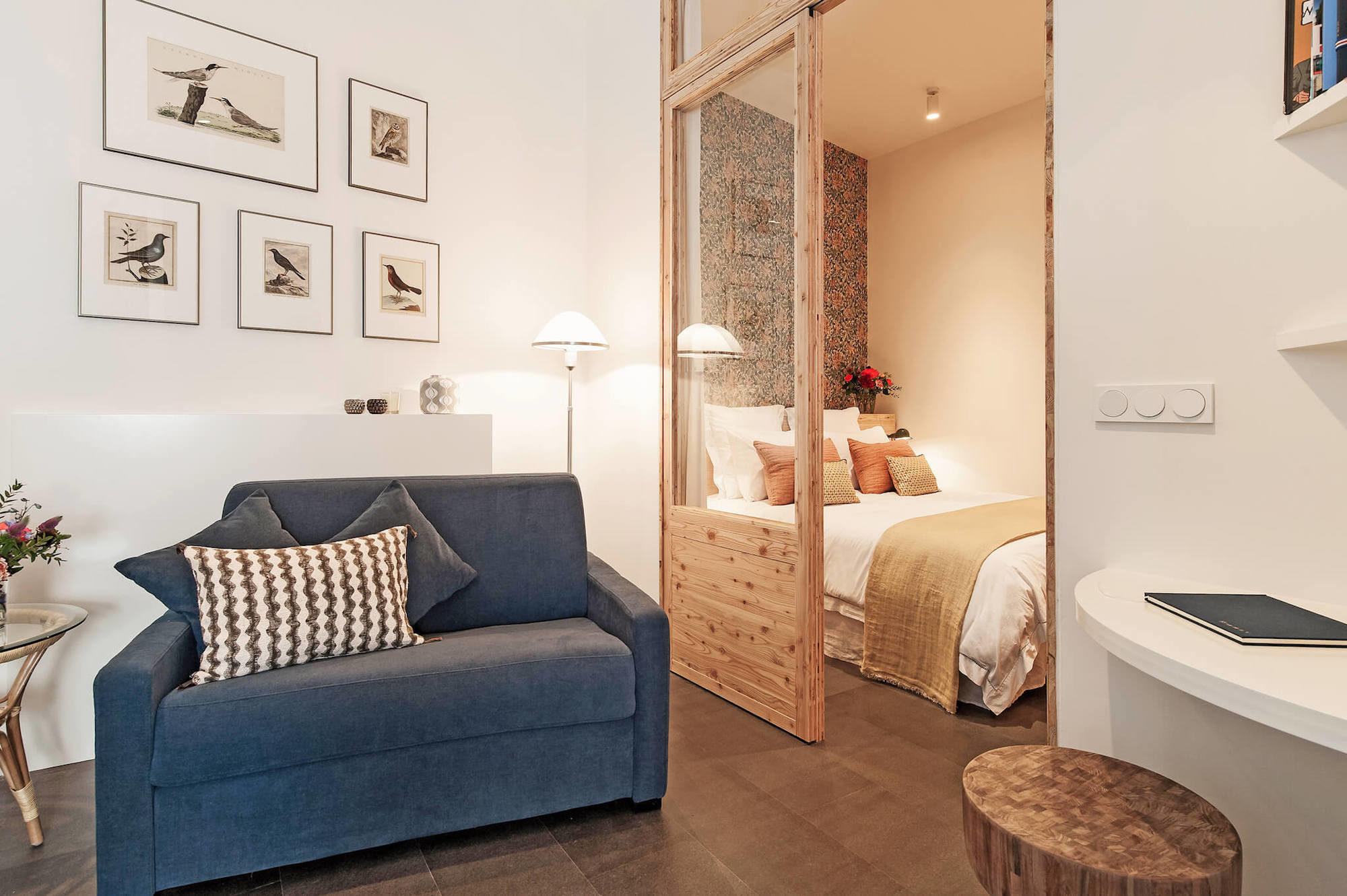 A beautiful rental apartment in Paris' Hotel de Ville area with a blue armchair, bird pictures up on the walls and a cozy double bed in the bedroom.