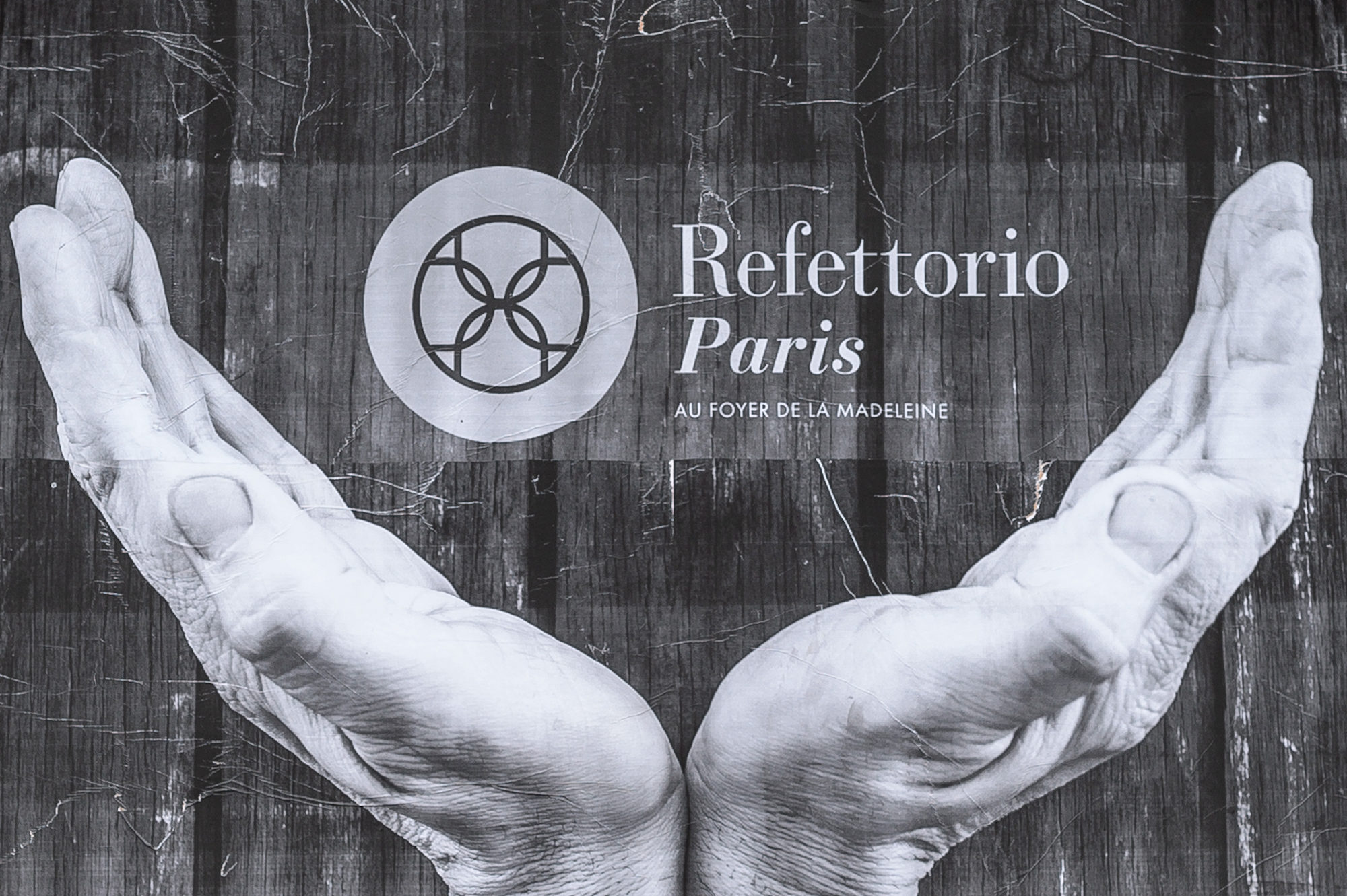 A poster for Refettorio restaurant in Paris, in the Madeleine Church crypt, serves meals to those in need.