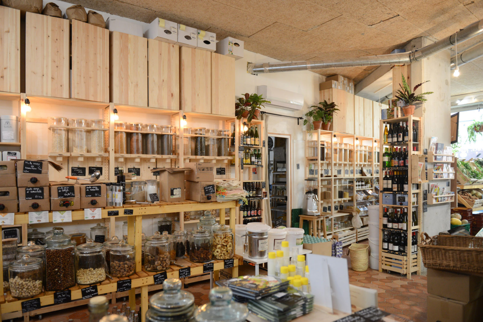 Inside L'Epicerie Kilogramme, a zero-waste, bulk-buying store in Paris, with pleasant interiors of timber shelves and cupboards of foodstuffs in jars.