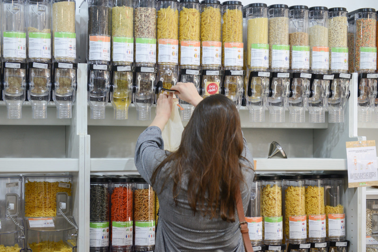 For zero-waste shopping in Paris, head to Day by Day, like this woman helping herself to pasta in bulk.