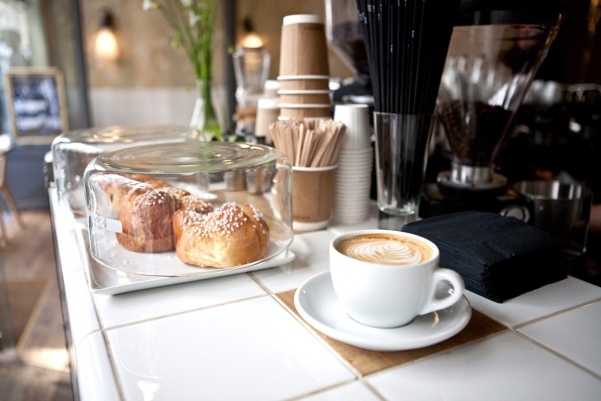 A cappuccino in a white cup and saucer on a tiled counter next to sugar-sprinkled brioche at Coutume gluten-free coffee shop in Paris.