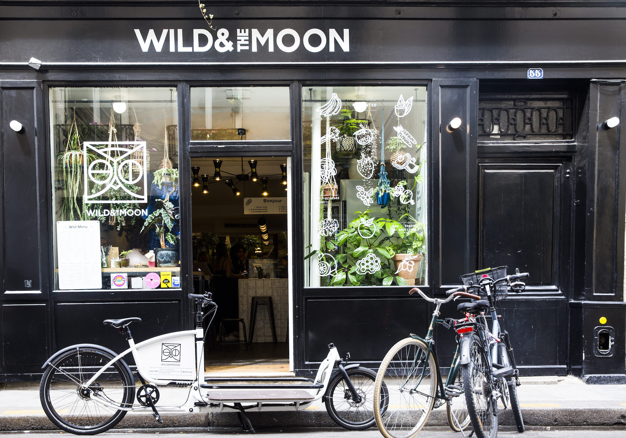 The window of Wild and the Moon gluten-free coffee shop in Paris with its black paneling and plants in the window and bikes parked outside.