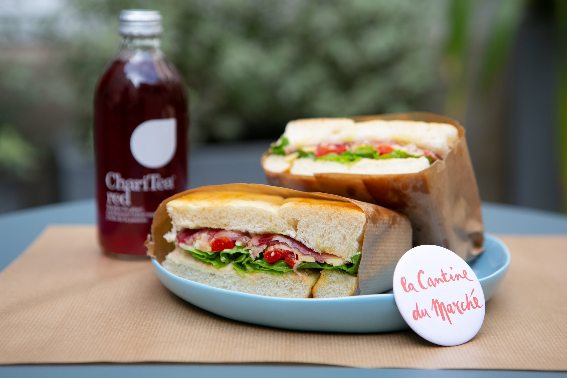 Sustainable food in Paris at La Cantine du Marché, where they serve fresh-pressed juices and teas like this Chari Tea, and homemade ham salad sandwiches on a blue plate.