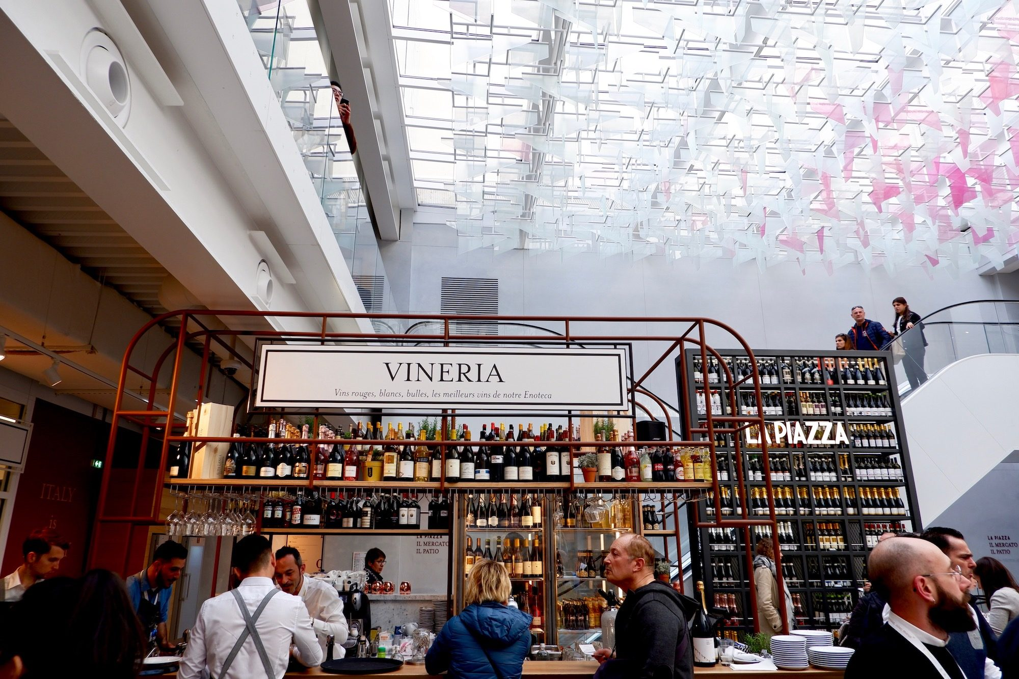 The wine bar at Eataly, the place to go for Italian food in Paris sits under a glass roof, through which the light filters through, even on a dull day.
