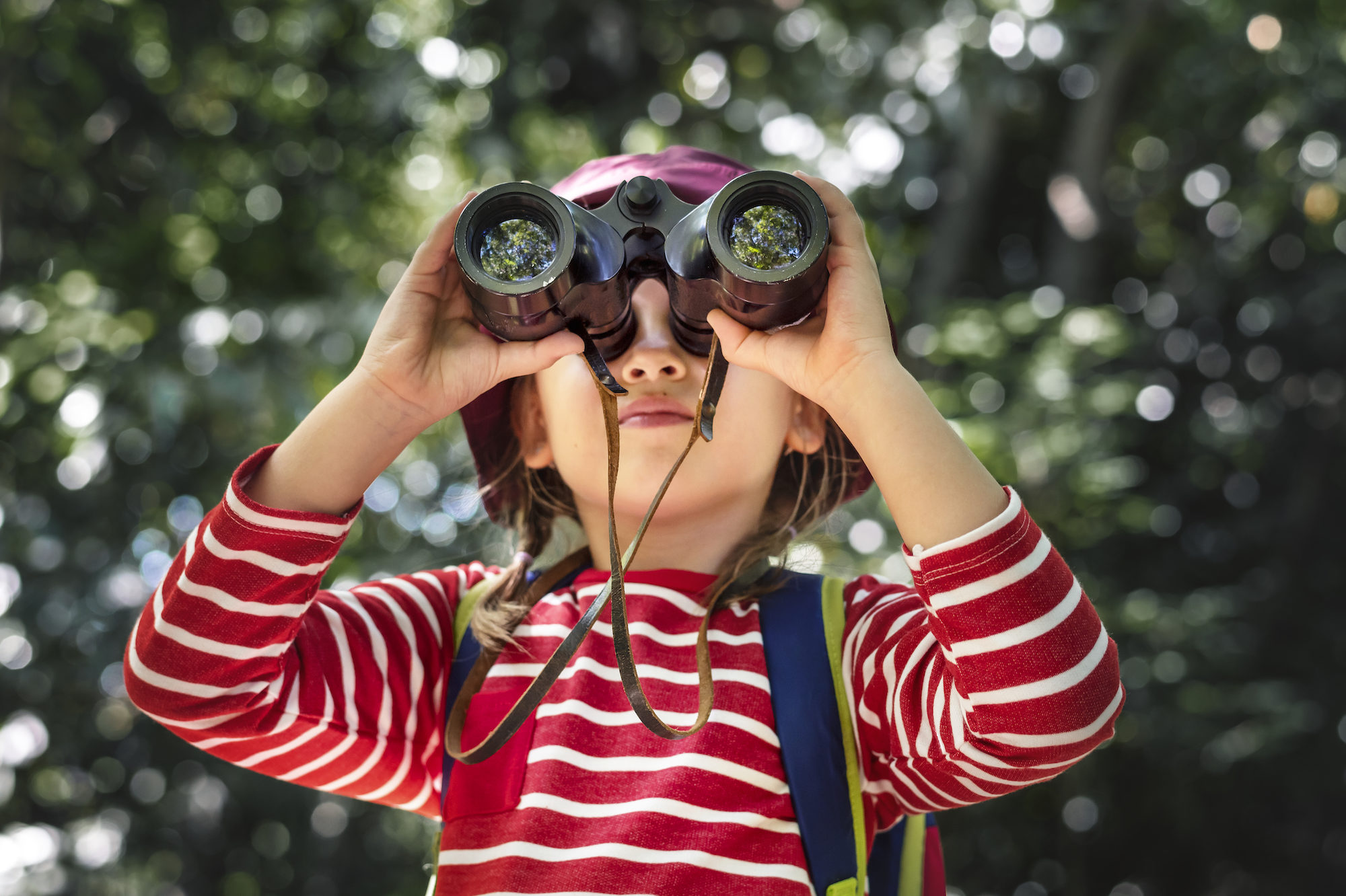 A little girl in a stripy red and white top, looking for Easter eggs in Paris, through a pair of binoculars.