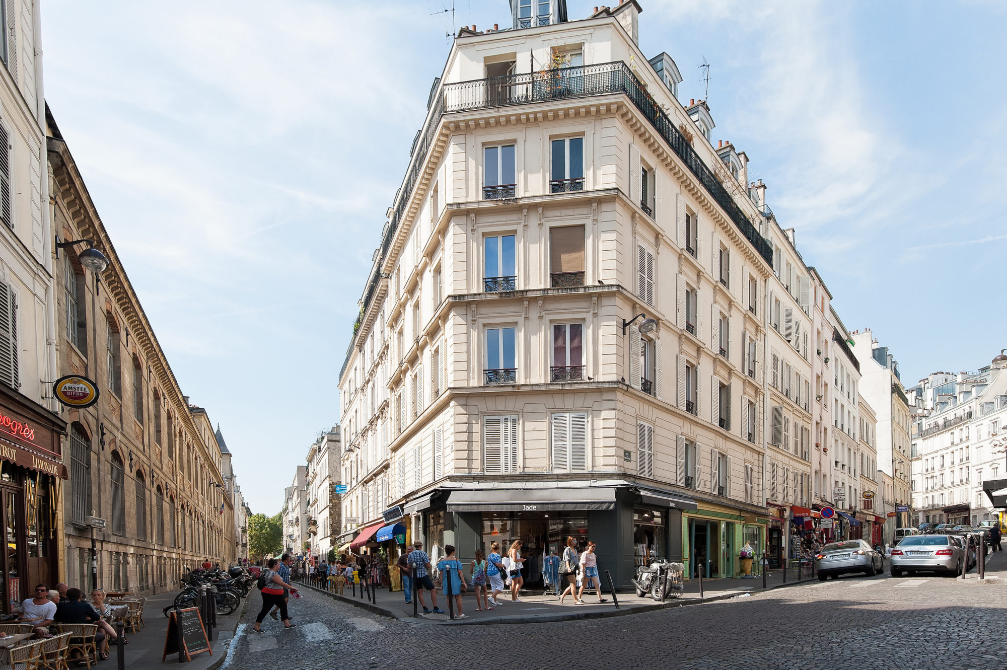 A street forking around  cream-colored iron-shaped building in Paris in summer, with people outside enjoying the sunshine.