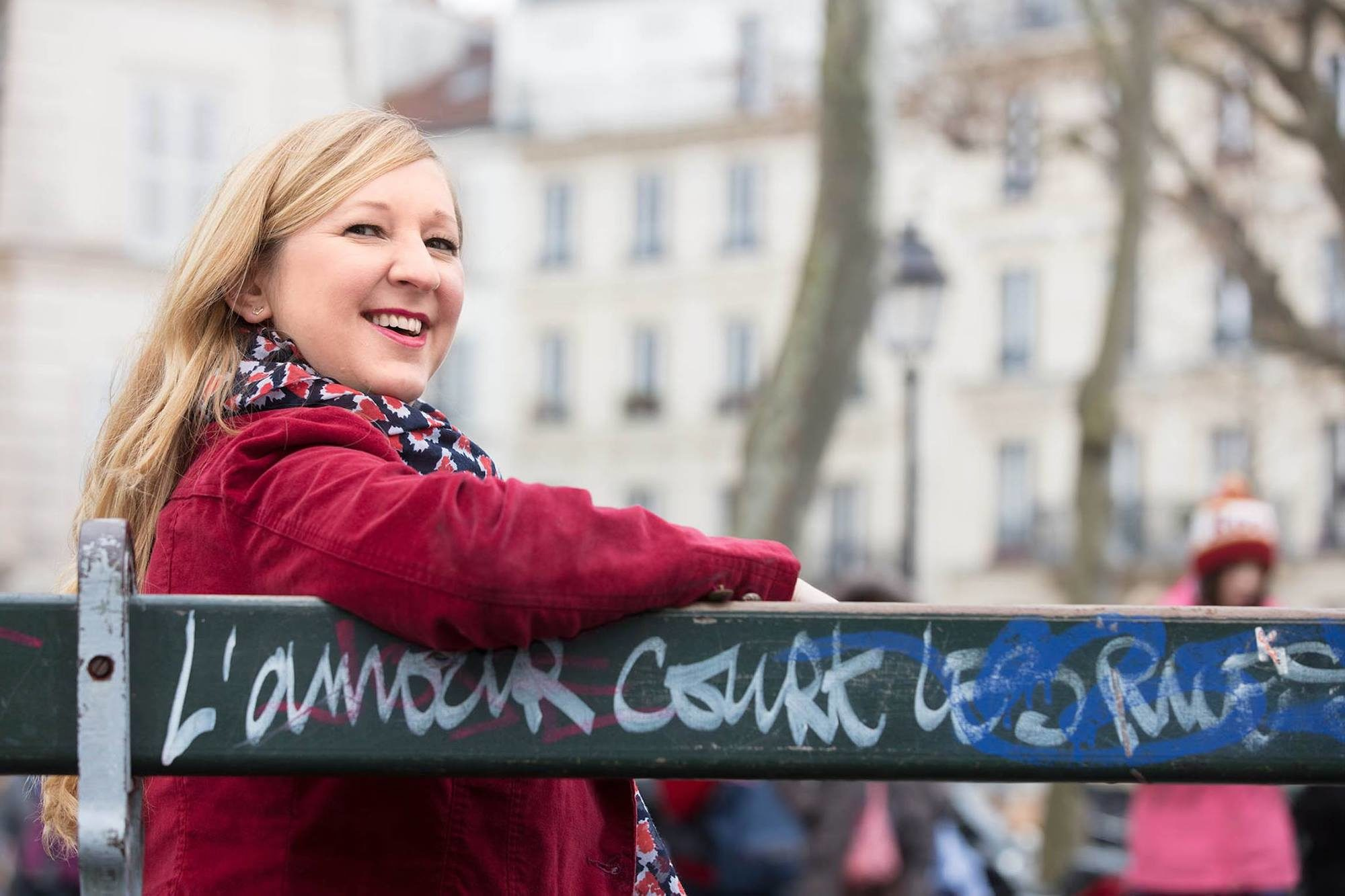 Expat blogger Lily Heise wearing a red jacket, sat on a Paris bench where the often-seen slogan 'Love runs through the streets' painted on it. She is smiling at the camera.
