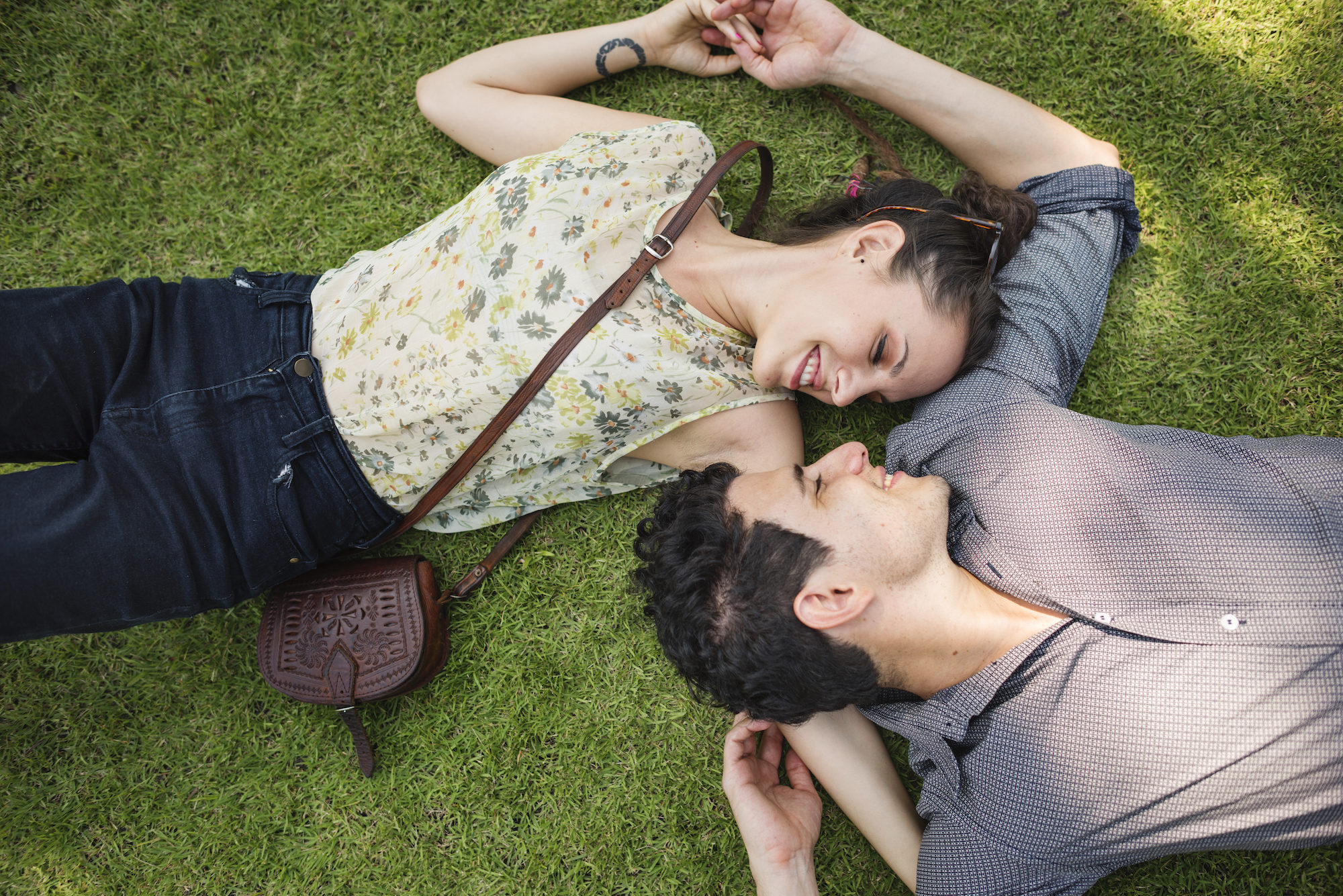 A couple holding hands and smiling at one another while lying on the grass.