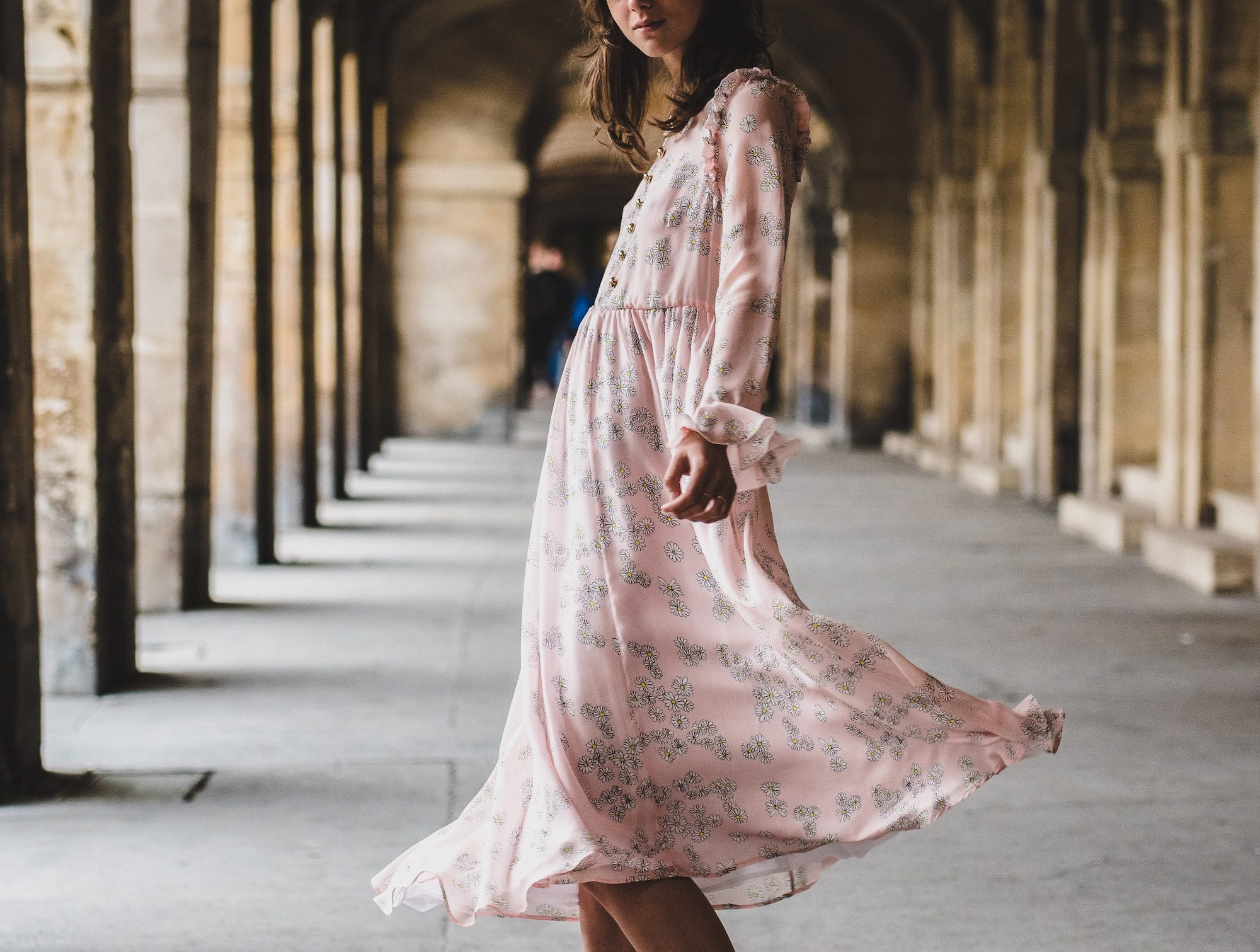 Luxury shopping in Paris made easy with these tips, including how to find stylish bohemian dresses like this one on a woman standing under the arches of the Palais Royal Gardens.
