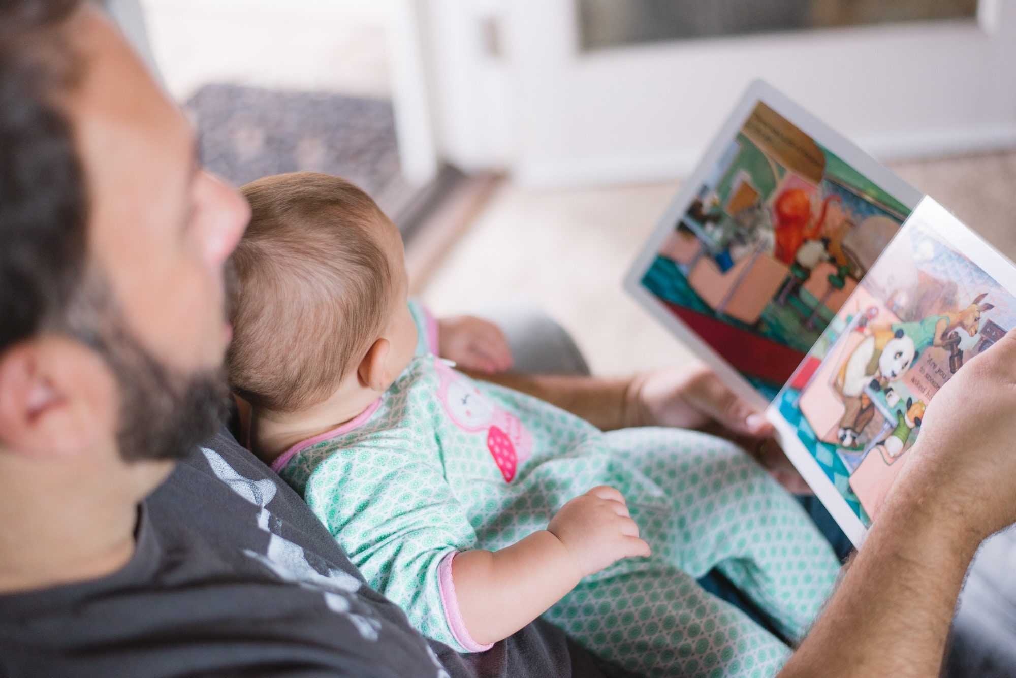 A father reading to his baby.