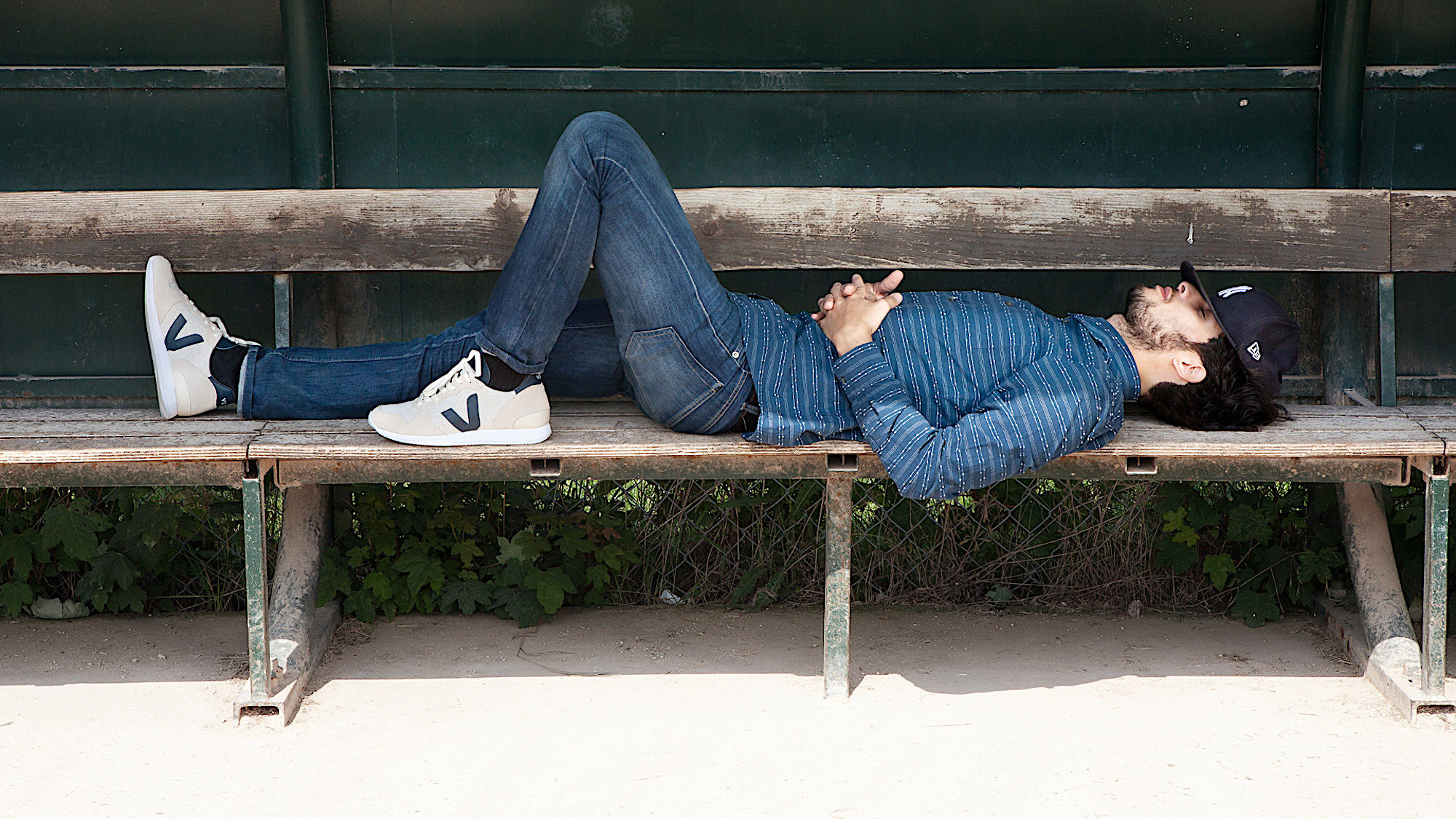 Sustainably made Veja trainers are also go-tos for Parisian men, like this young man wearing jeans and blue shirt, lying on a bench sleeping.