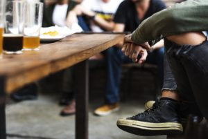 A group of friends enjoying a beer with young person with tattooed fingers in foreground.