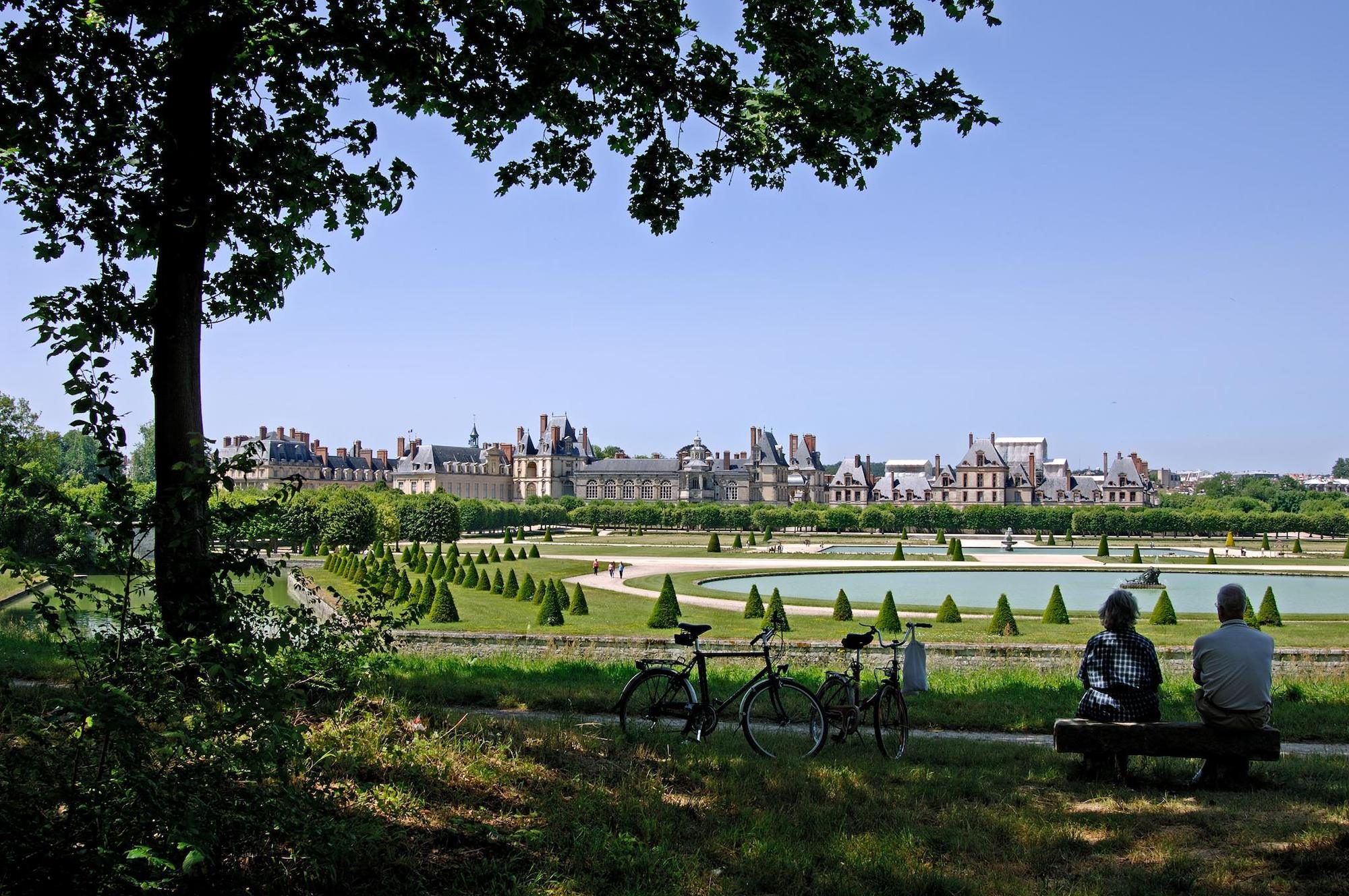 A view of the Château de Fontainebleau from the park, two people have parked their bikes and are admiring the view while sitting on a bench.