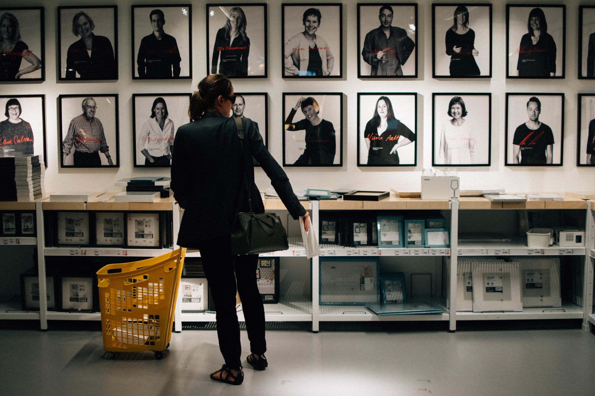 A customer standing in front of framed black and white posters at Ikea Paris La Madeleine