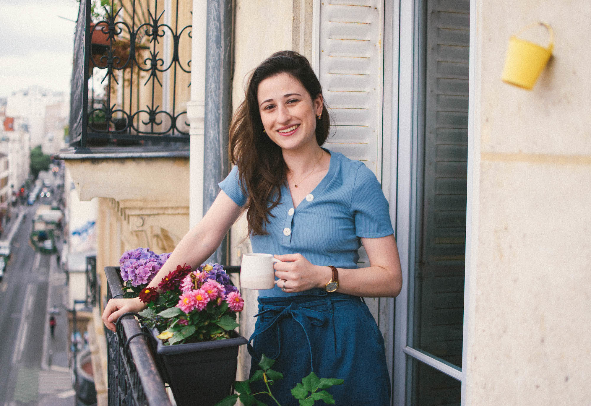 Lindsey Tramuta standing on her balcony in her apartment in Paris' 11th arrondissement.