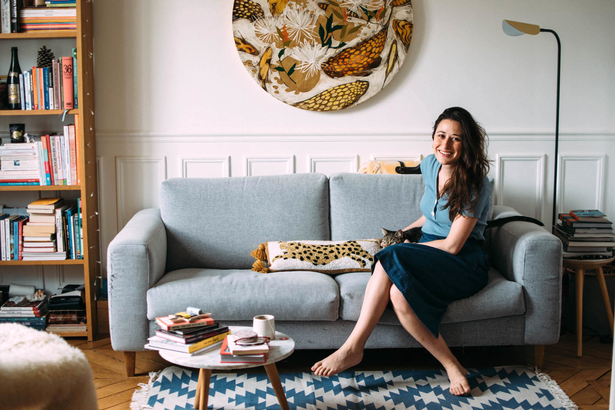 Lindsey Tramuta relaxing in her living room with one of her cats in Paris' 11th arrondissement.
