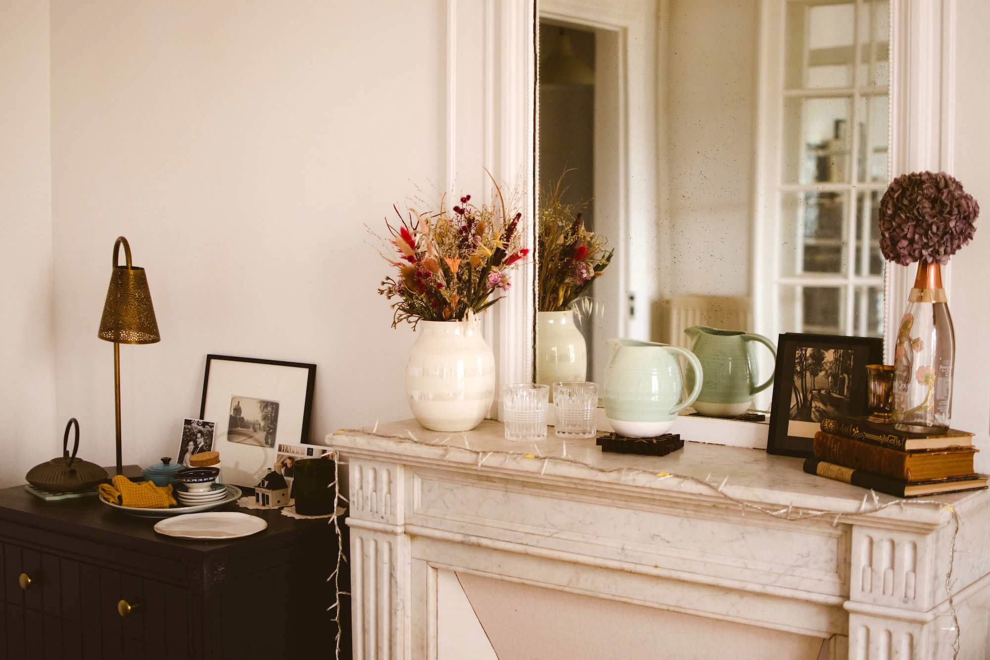 A pretty apartment corner with dried flowers, photographs, books, and a mirror in Lindsey Tramuta's home in Paris' 11th arrondissement.