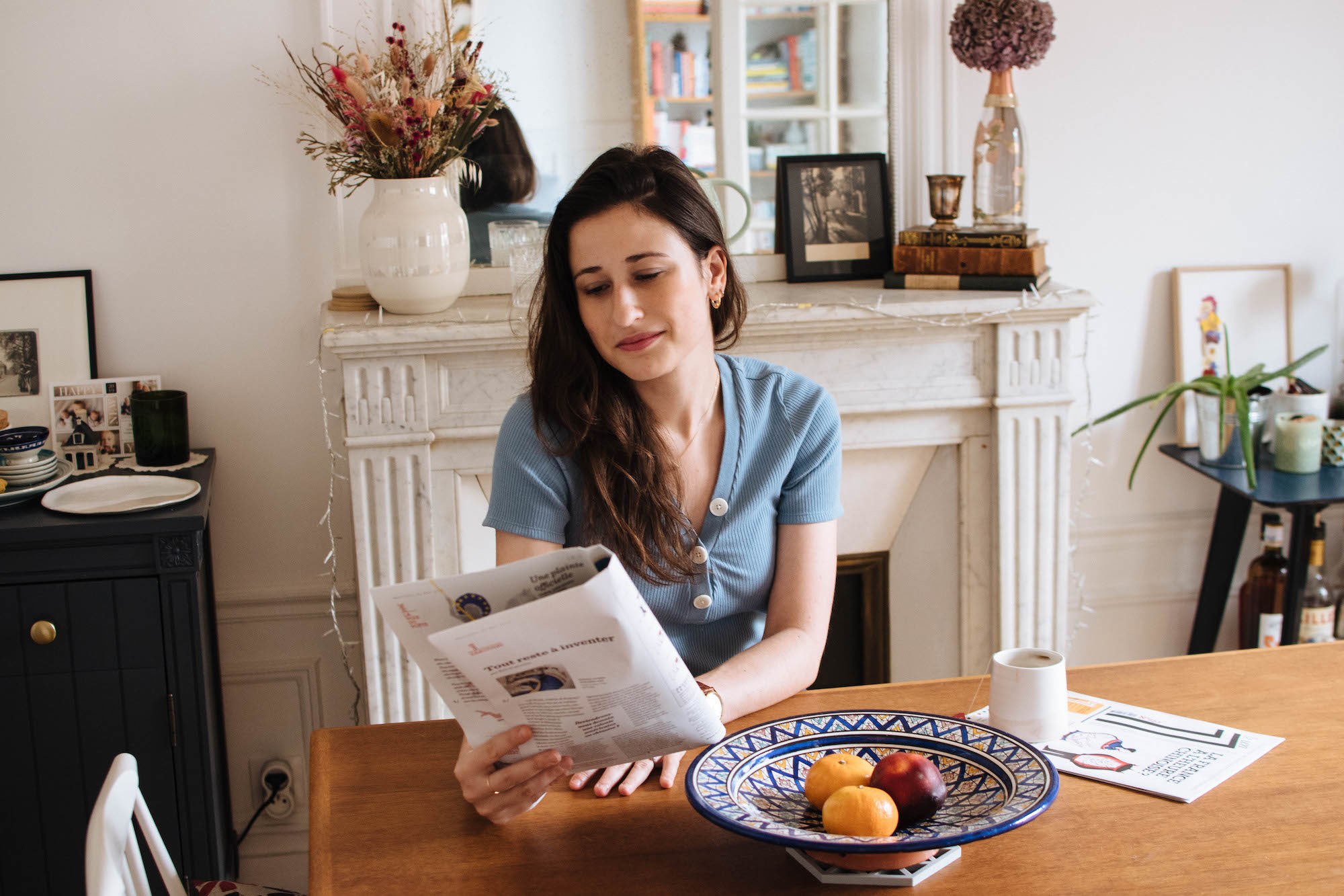 Lindsey Tramuta reading an edition of Le 1 Hebdo, a French weekly print newspaper, in her apartment in Paris' 11th arrondissement.