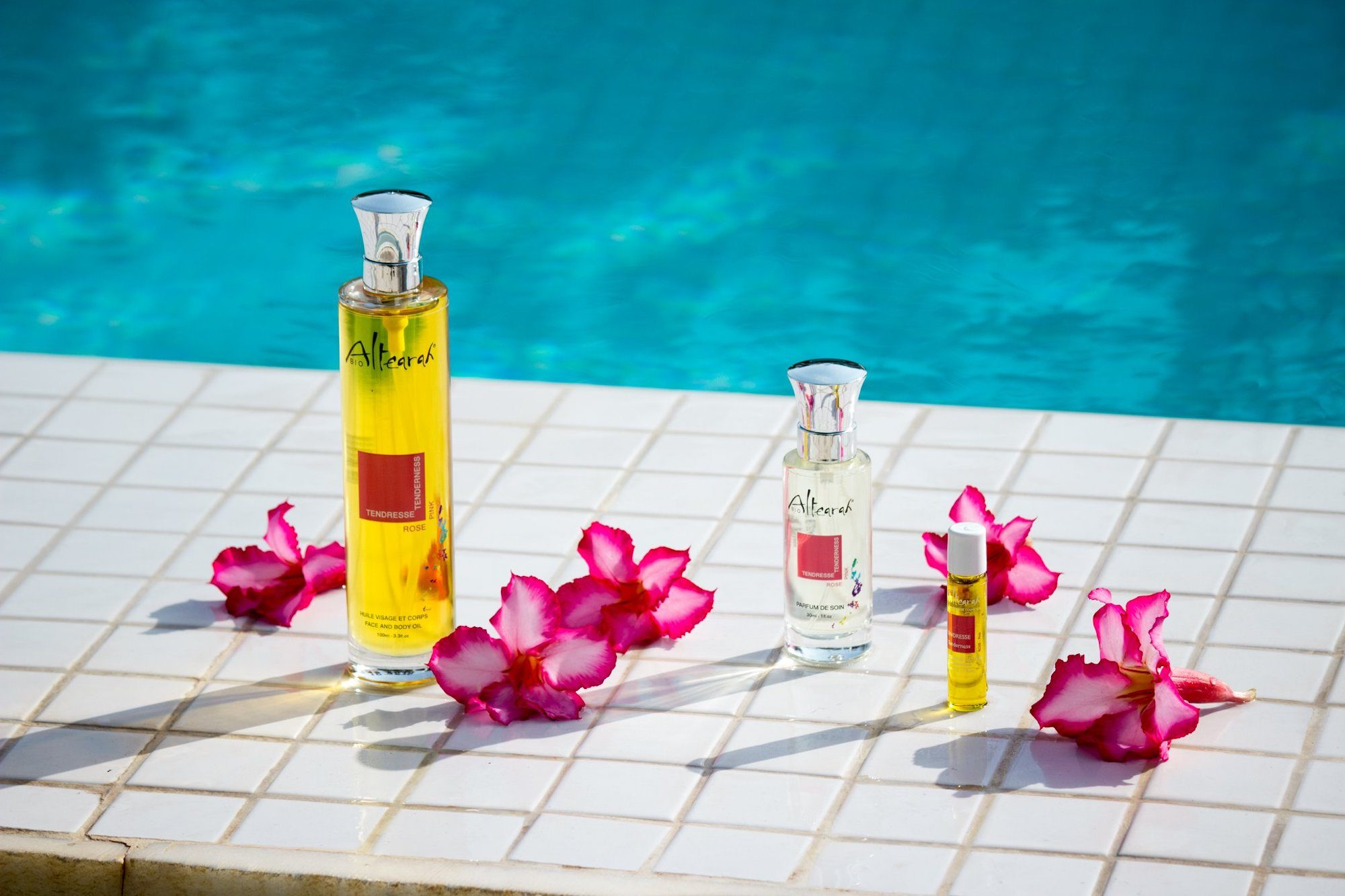 Altearah Bio organic perfume bottles standing by the side of a turquoise pool and among pink flowers.