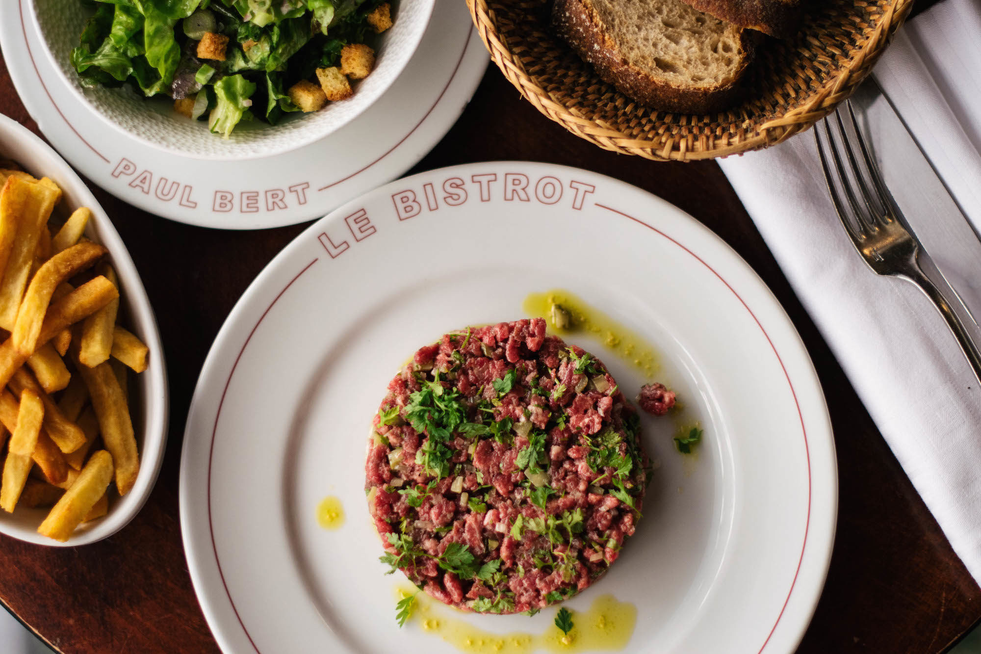 Signature steak tartare at the Bistrot Paul Bert in Paris with sides of bread, salad and fries.