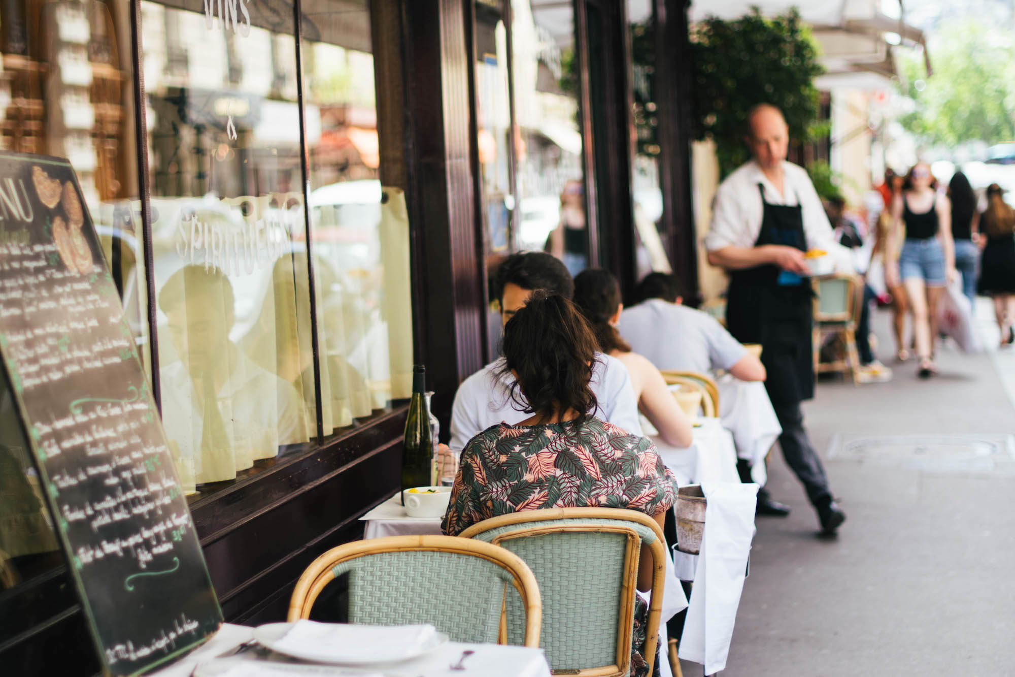 People eating out on a bistro terrace in summer in Paris.
