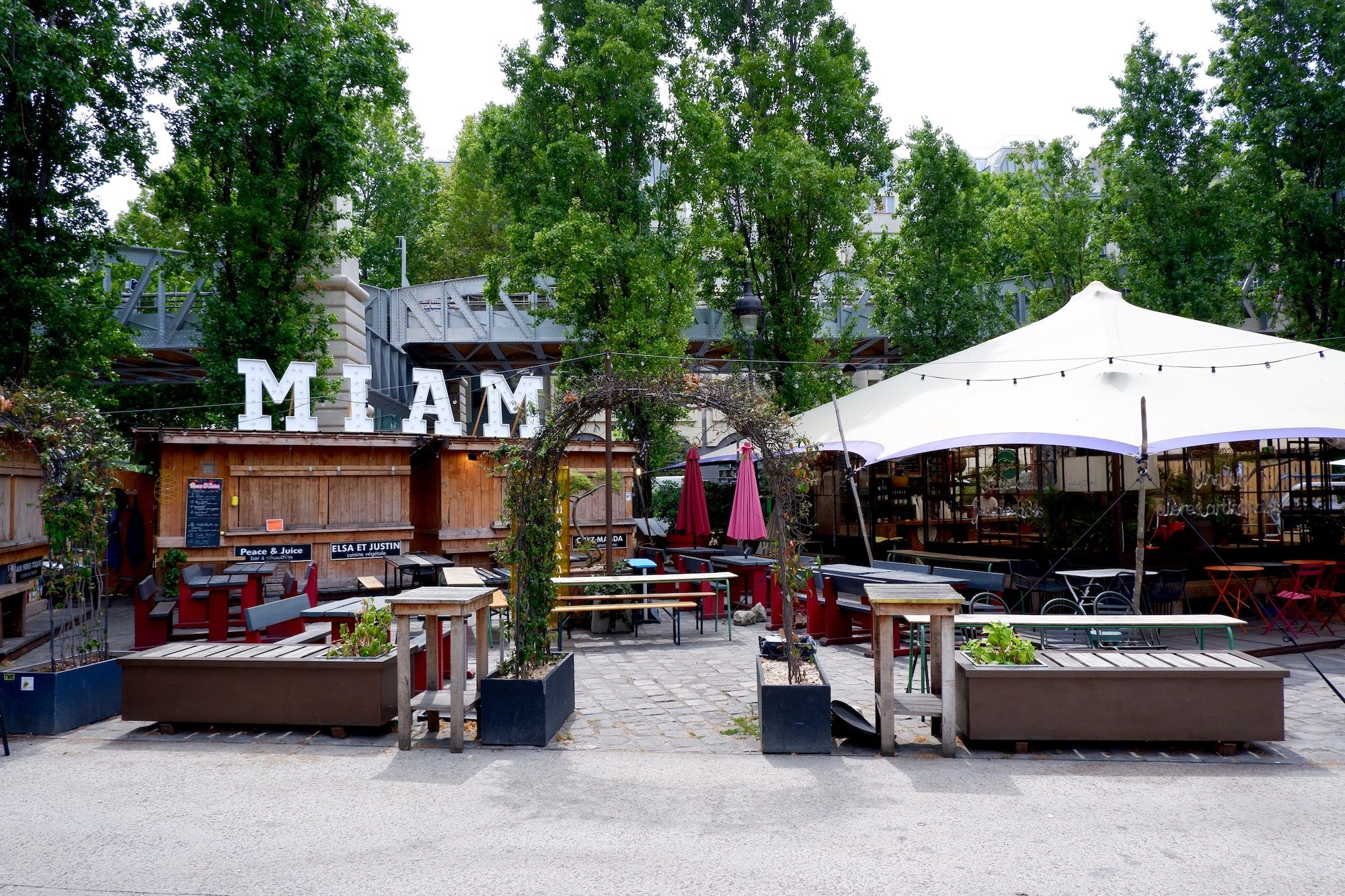 The terrace of La Rotonde Paris bar close to the canal is an urban garden with seating and parasols.