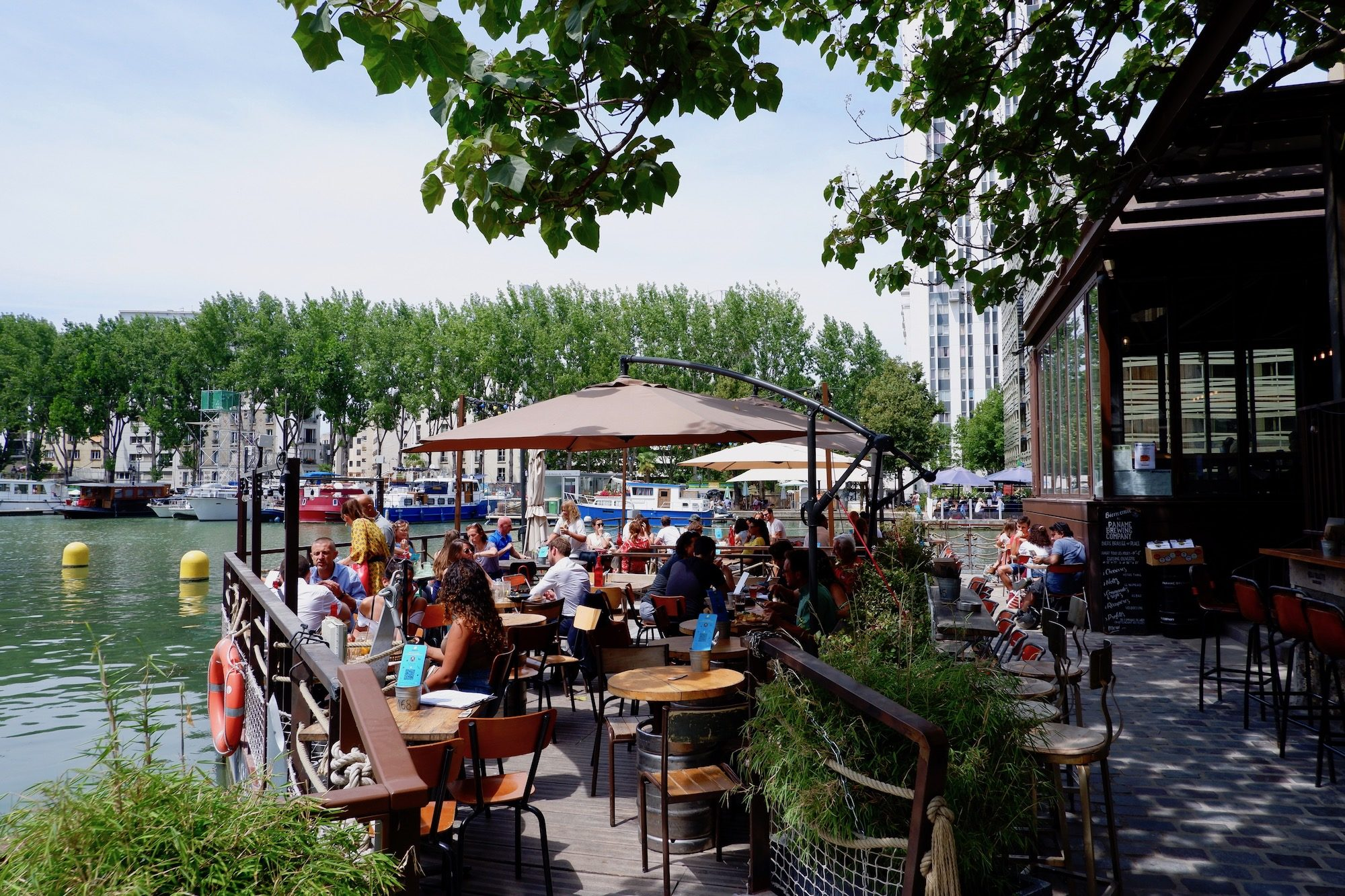 The terrace reaching out across the water of the Canal de l'Ourcq at the Paname Brewing Company in Paris on a sunny summer's day.