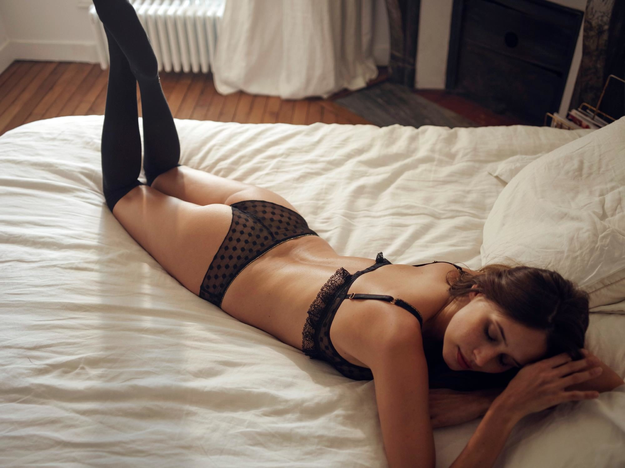 A woman wearing a matching bra and underwear with black knee-high socks from French fashion brand Ysé, lying on a bed.