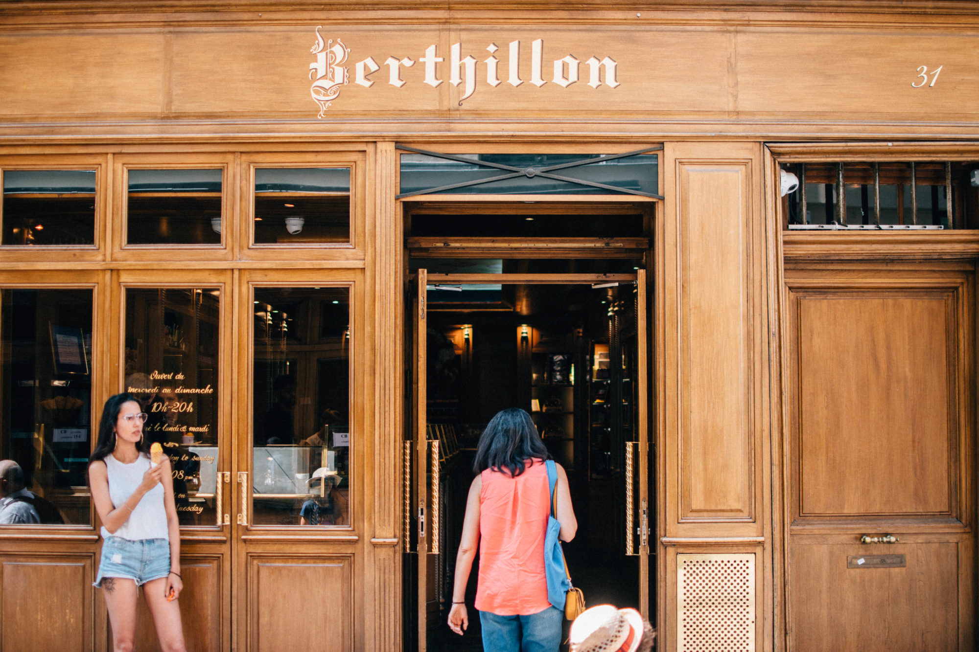 The wood-paneled exterior of one Paris's Berthillon ice cream shops with a young woman standing outside, enjoying one of their soft ice creams.